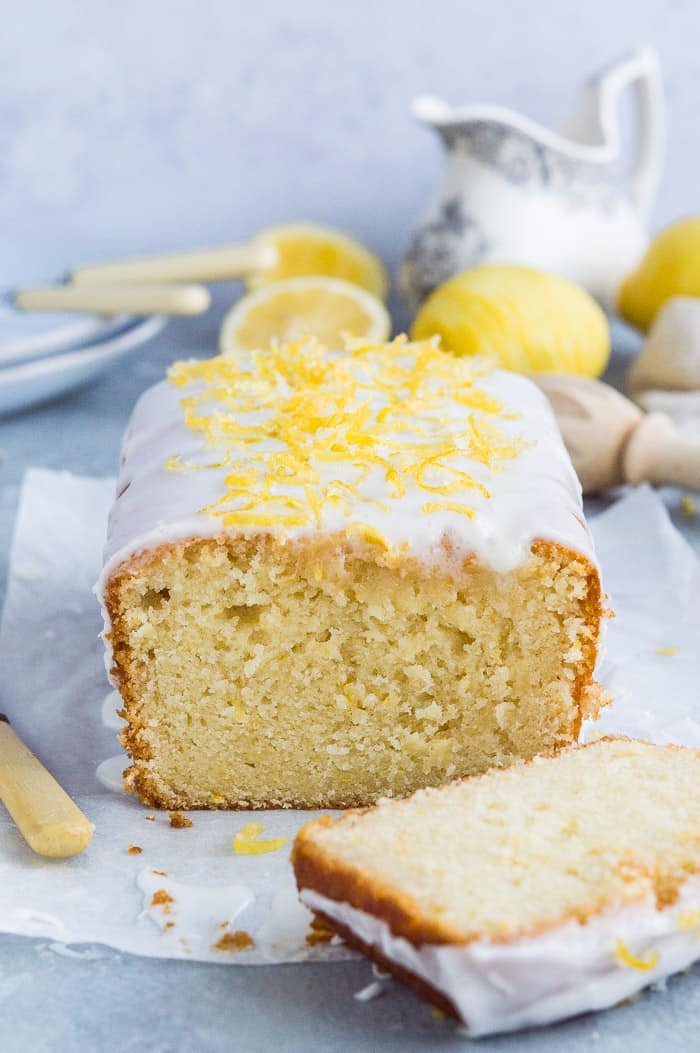 Close up of the end of a loaf of sliced lemon drizzle cake with lemons and crockery in the background.