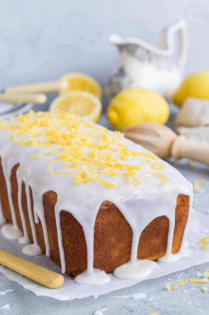 Close up of the end of an unsliced loaf of vegan lemon drizzle cake topped with lemon glaze and lemon zest.
