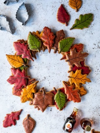 Autumn leaf maple cookie wreath on a white background with coloured leaf cookies, cookie cutters and bottles of maple syrup.