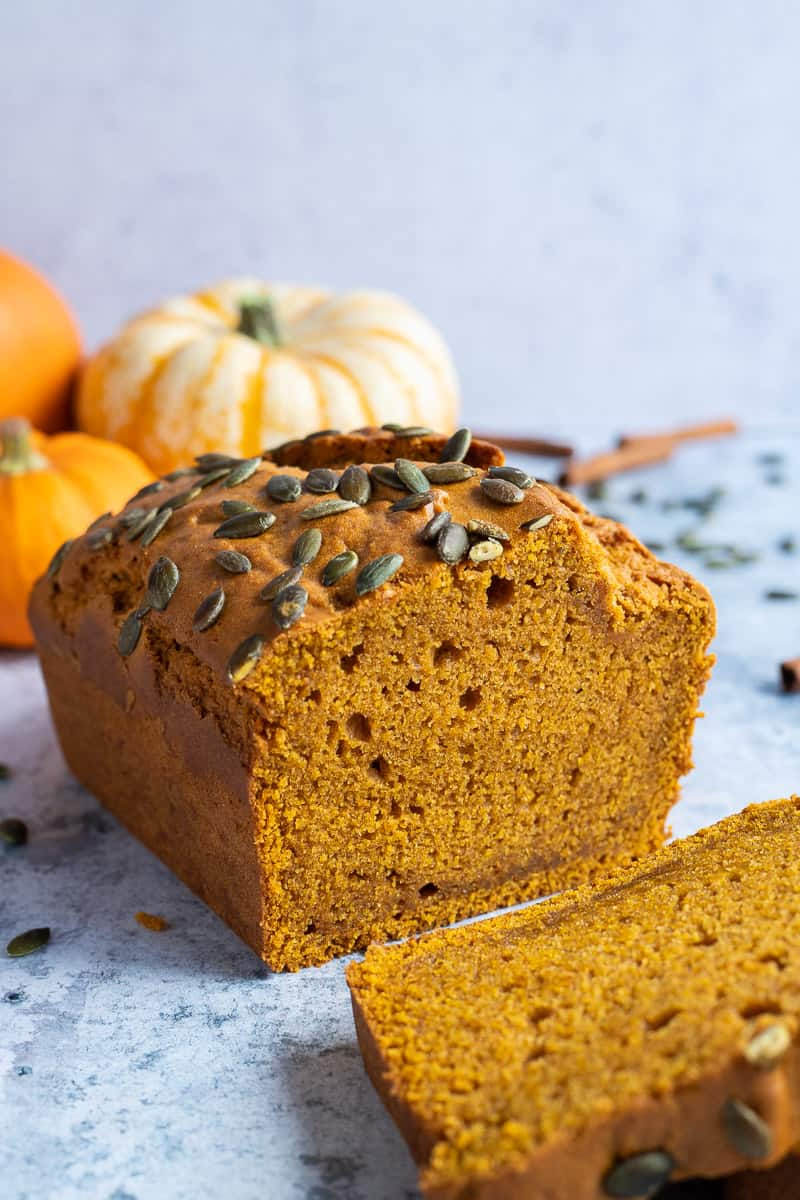 The end of a sliced loaf of vegan pumpkin cake with mini pumpkins in the background.