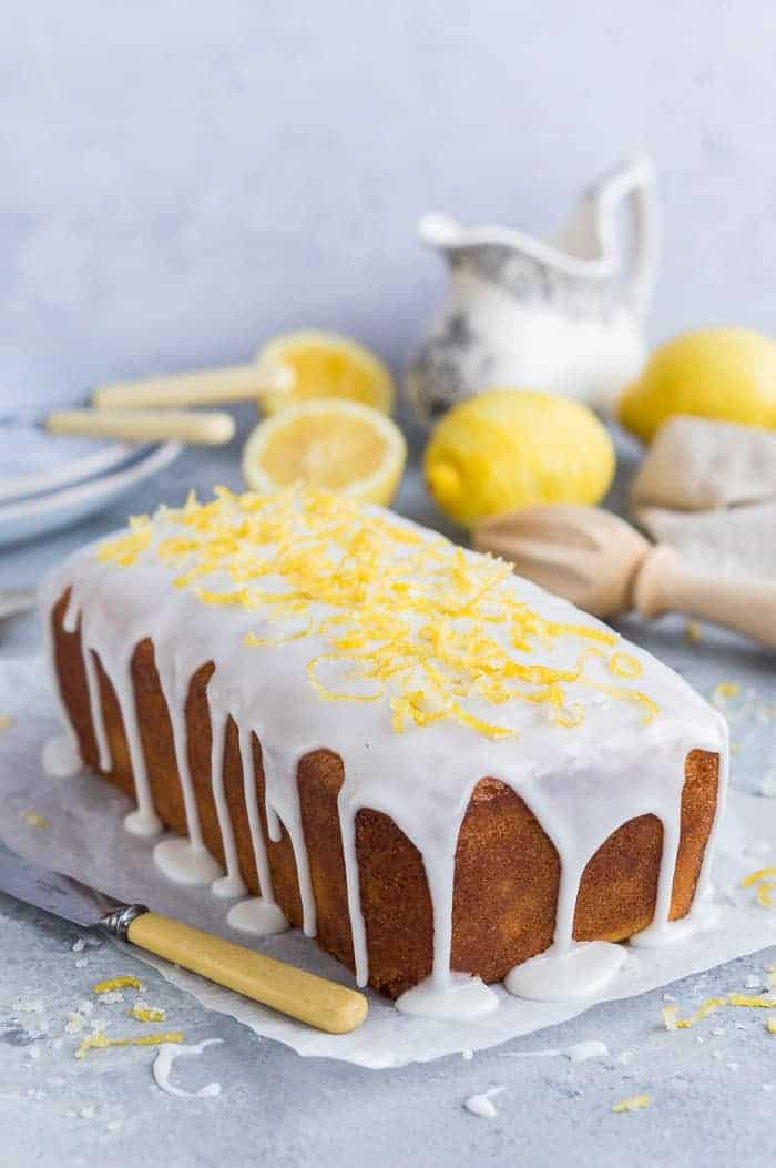Vegan lemon drizzle cake with lemon glaze and candied lemon zest on a sheet of baking parchment with lemons and crockery in the background.