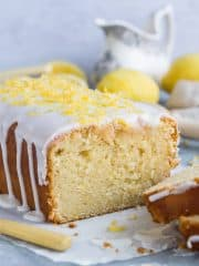 Close up of the end of a sliced vegan lemon drizzle loaf cake topped with lemon glaze and sugared lemon zest.