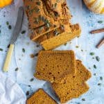 a loaf of vegan pumpkin bread topped with pumpkin seeds on a sheet of baking parchment on a blue background with mini pumpkins, cinnamon sticks, a grey cloth and a knife.