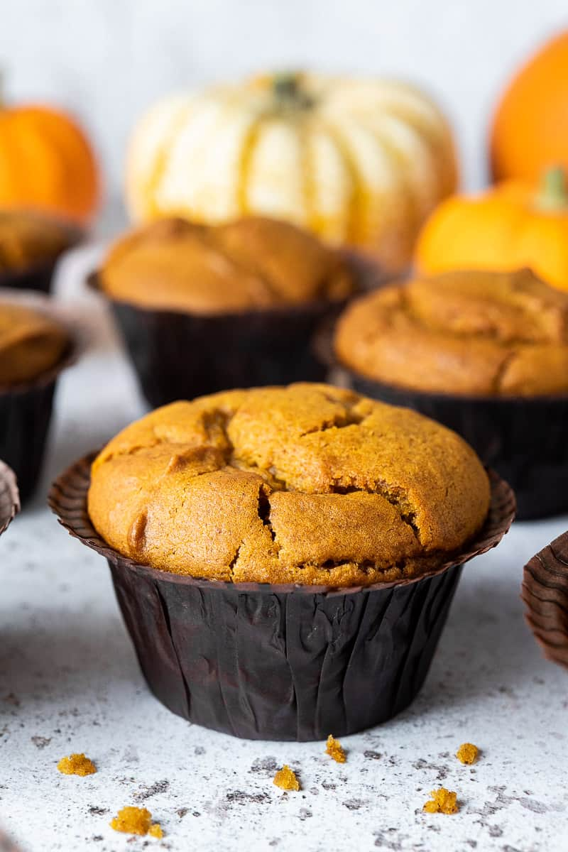Close up of a vegan pumpkin muffin in a brown muffin liner.