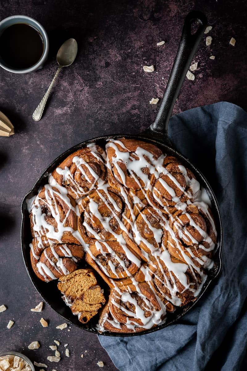 a cast iron skillet of vegan gingerbread cinnamon rolls, one sliced in half, on a dark background with candied ginger and a grey cloth.