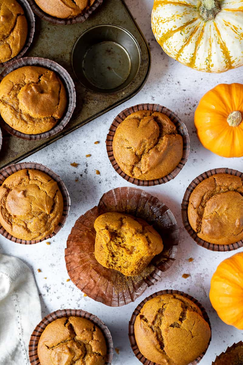 Vegan pumpkin muffins on a white surface, one with a bite taken out of it, surrounded by mini pumpkins and a muffin tray.