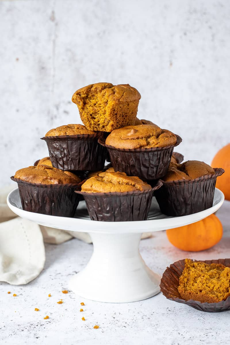 A stack of pumpkin muffins on a white cake stand.