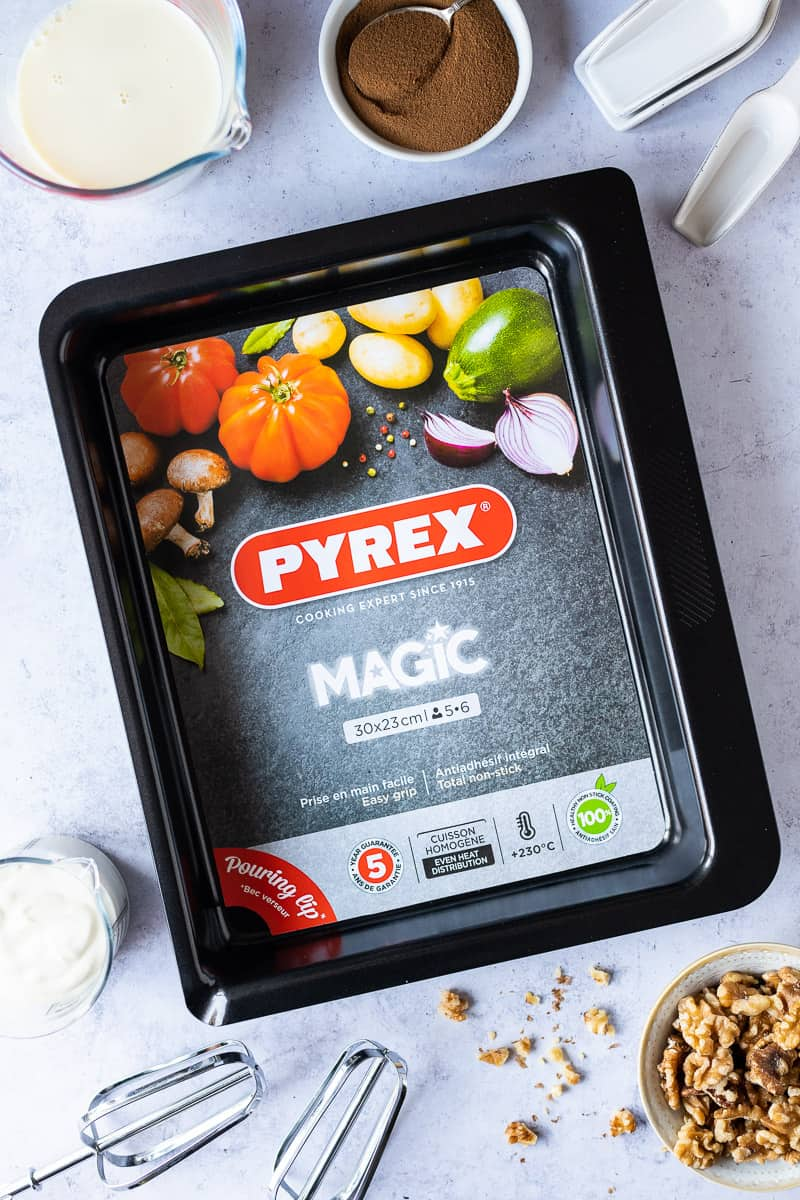 Pyrex magic metal roasting tin surrounded by baking equipment and ingredients.