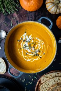 A panful of spiced carrot and pumpkin soup with a swirl of cream and pumpkin seeds on a dark background with mini pumpkins and slices of bread.