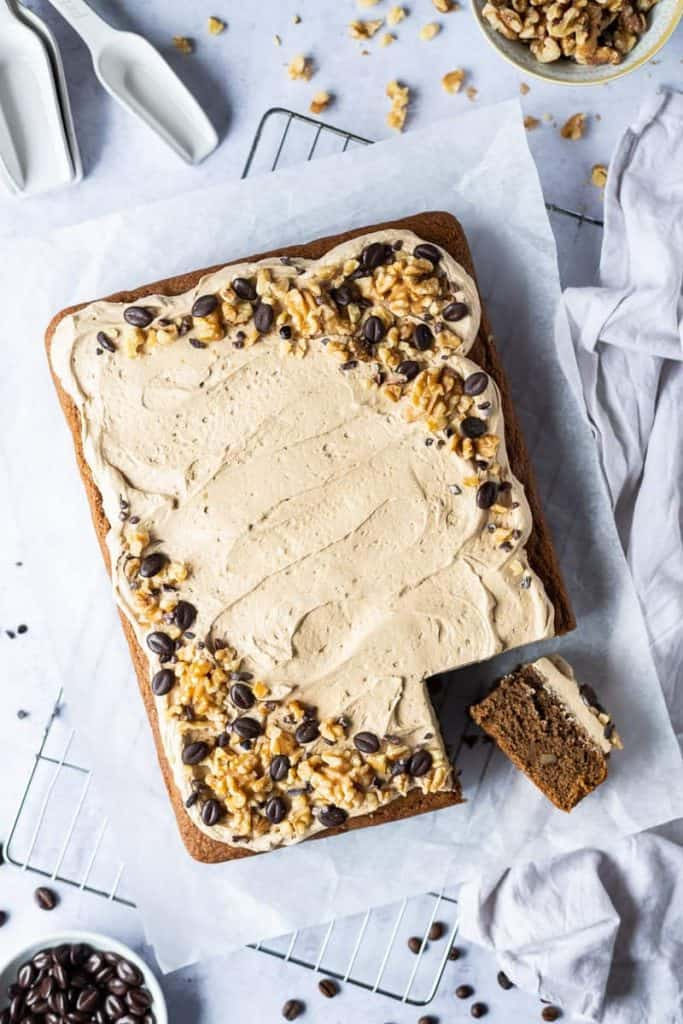 Vegan coffee and walnut traybake cake with a slice cut out on a sheet of baking parchment on a wire rack with chocolate coffee beans and chopped walnuts.