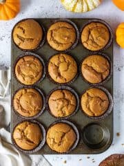 A tray of vegan pumpkin muffins on a white surface with mini fresh pumpkins.