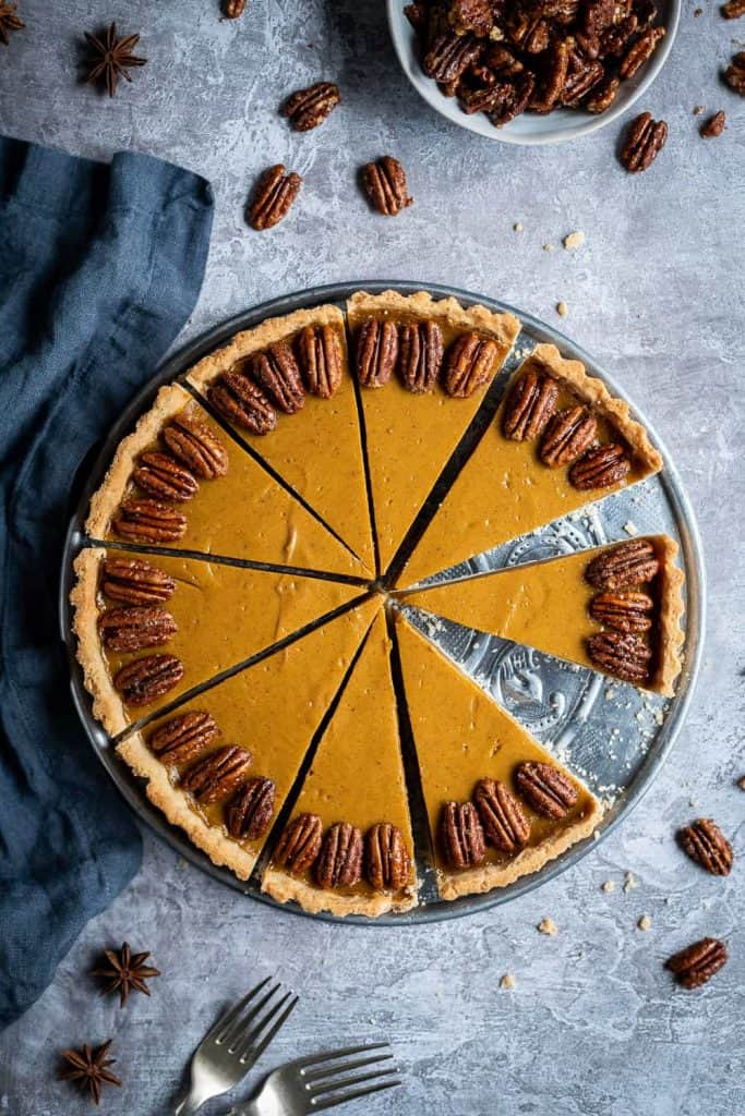 vegan pumpkin pie on a metal plate on a grey background with maple pecans.
