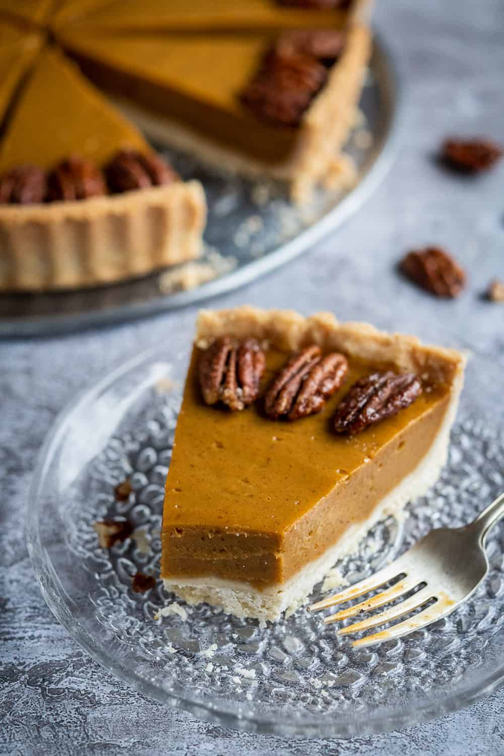 close up of a slice of vegan pumpkin pie with a forkful removed.