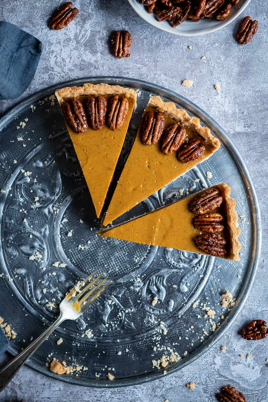 Three slices of vegan pumpkin pie on a metal plate.