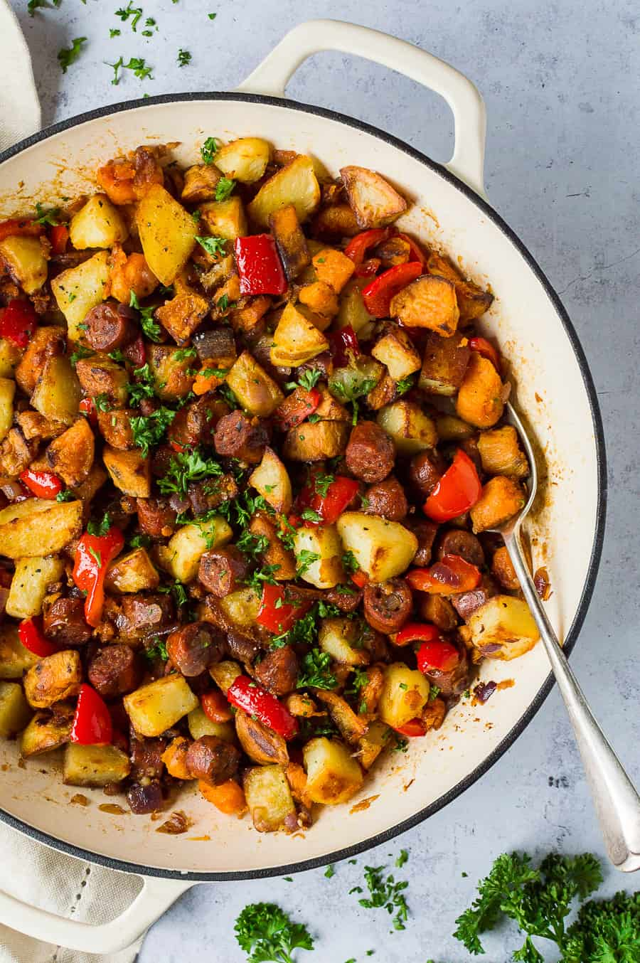 vegan chorizo and potato hash in a white pan on a grey background.