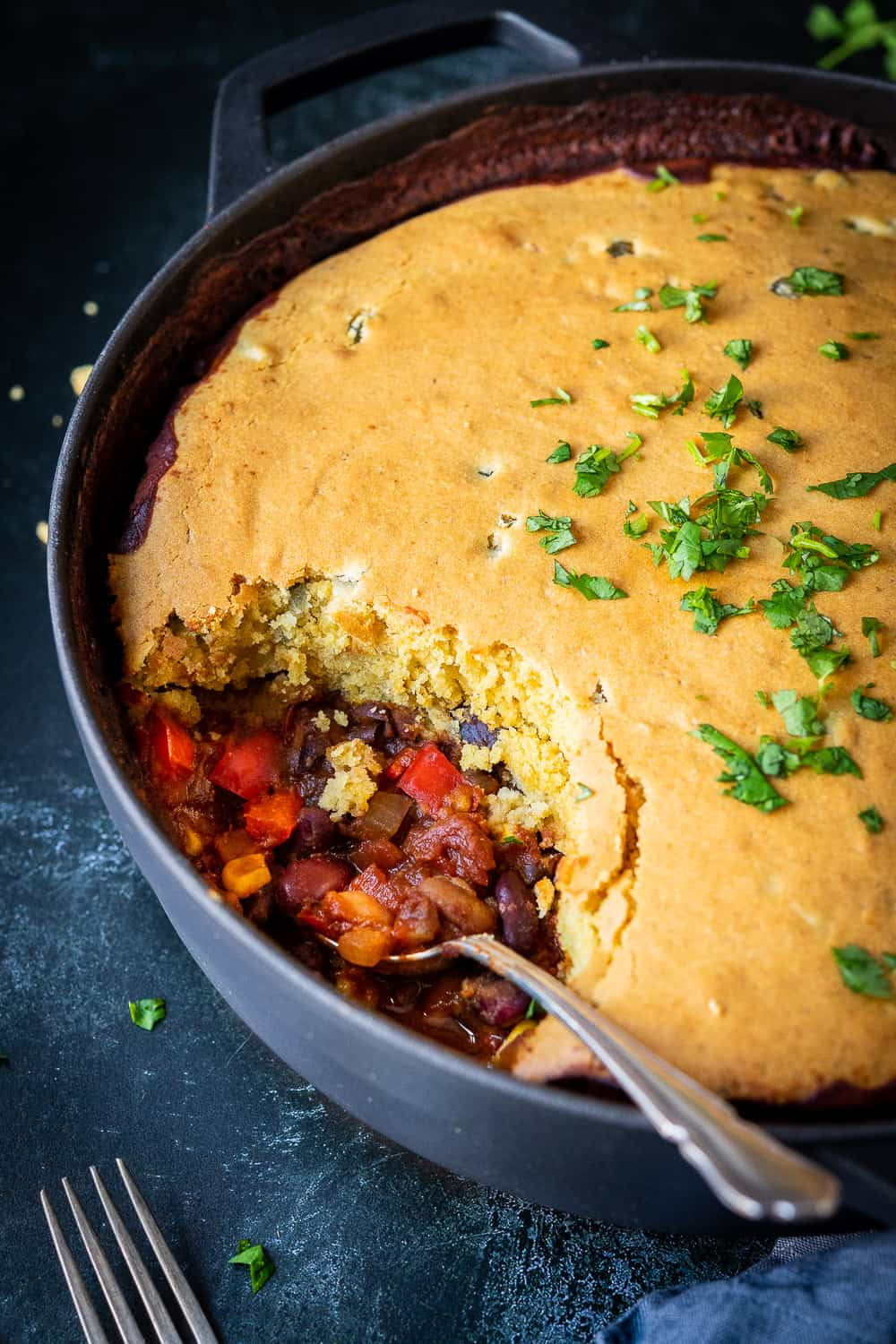 Side shot of vegan chilli cornbread pie with a spoonful removed and a spoon sitting in the dish.