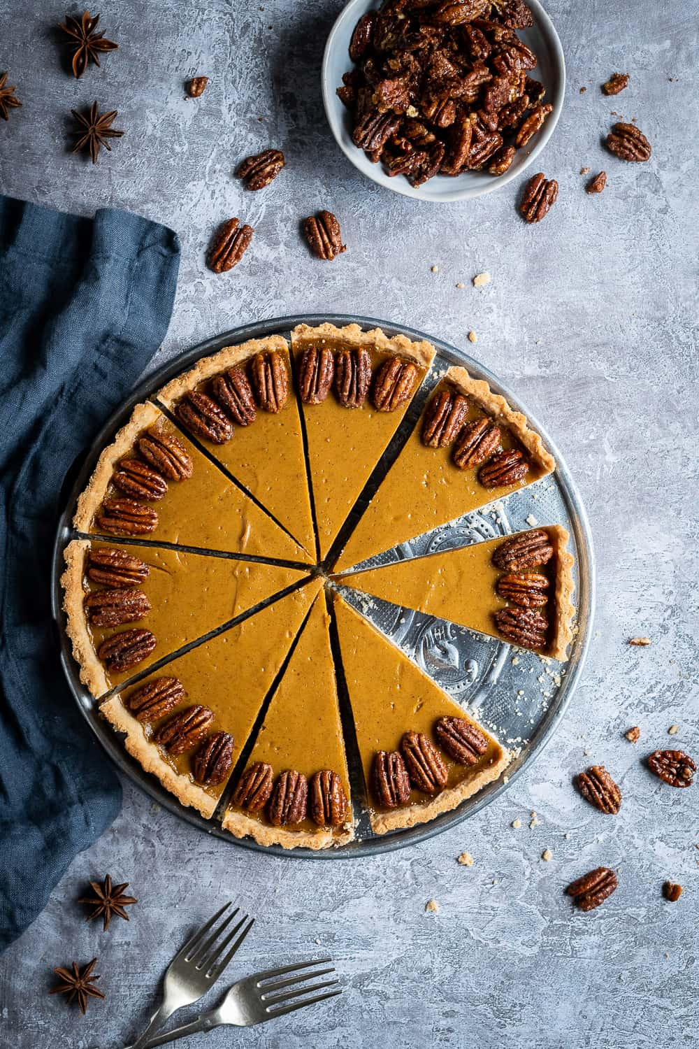 vegan pumpkin pie on a grey background with a bowl of maple roated pecans, two forks and a blue cloth.