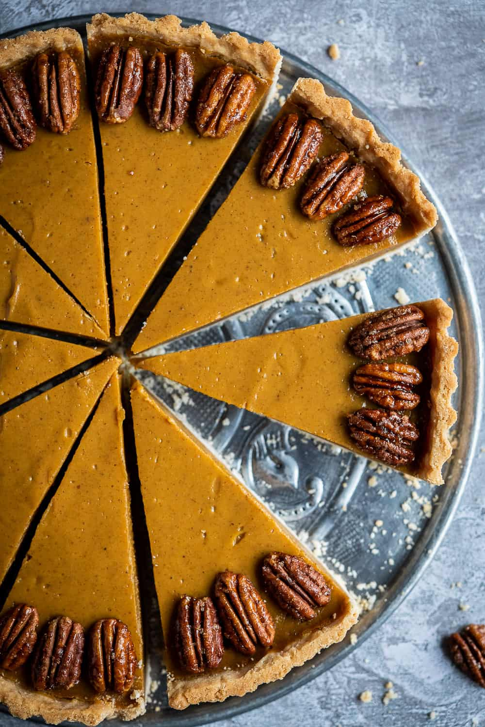 close up of vegan pumpkin pie topped with maple pecans.