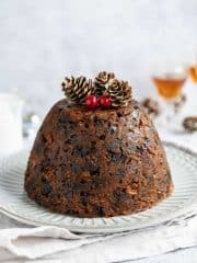 vegan Christmas pudding on a white plate on a light grey cloth.