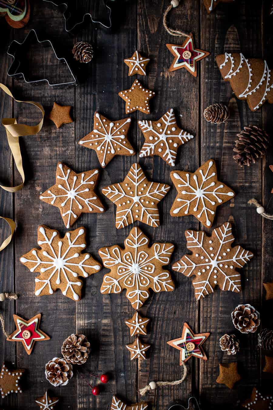 Vegan gingerbread snowflake cookies arranged in a christmas tree shape with pine cones and christmas decorations.