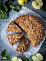 vegan apple cake on a square of white baking parchment on a grey background surrounded by apples and apple tree leaves.