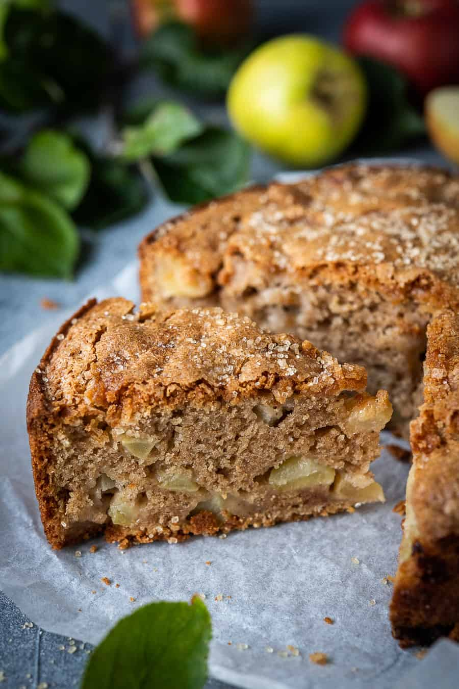 close up of a slice of vegan apple cake with apples and apple tree leaves in the background.
