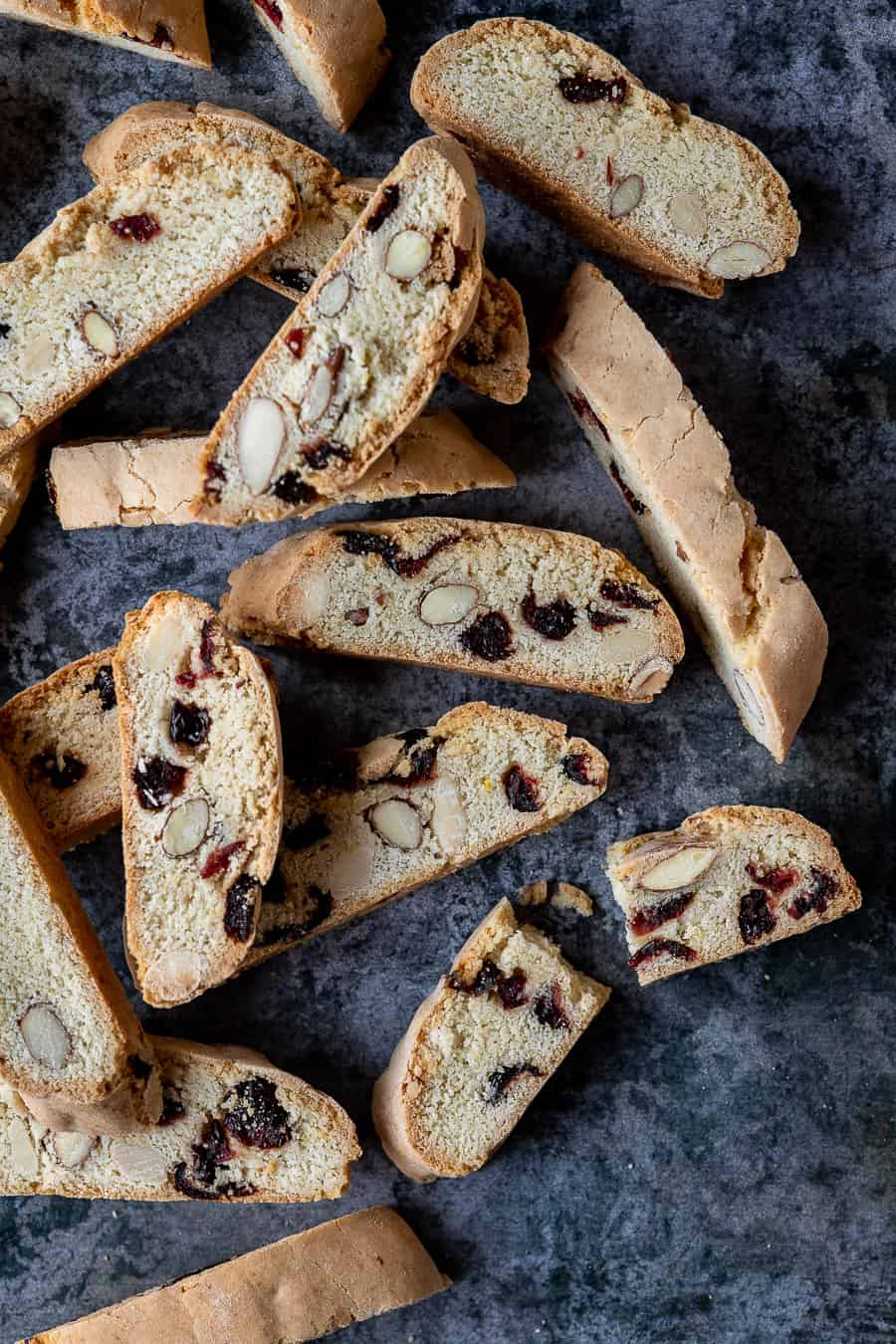 Vegan biscotti on a dark grey background, one broken in half.