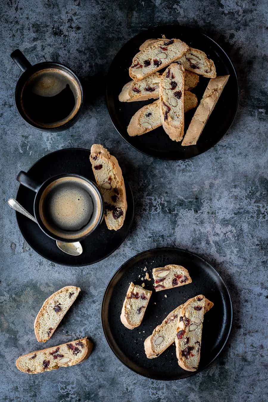 Vegan biscotti on two black plates with two black cups of coffee.