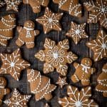 iced vegan gingerbread cookies on a dark wood background.
