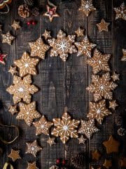 Vegan gingerbread snowflake cookies arranged in a wreath shape on a dark wood background with pine cones and Christmas decorations.