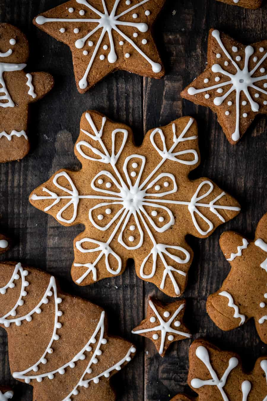 close up of a vegan gingerbread snowflake cookie with white icing on a dark wood background.
