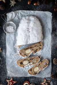 vegan stollen on a sheet of baking parchment on a black surface surrounded by christmas decorations.