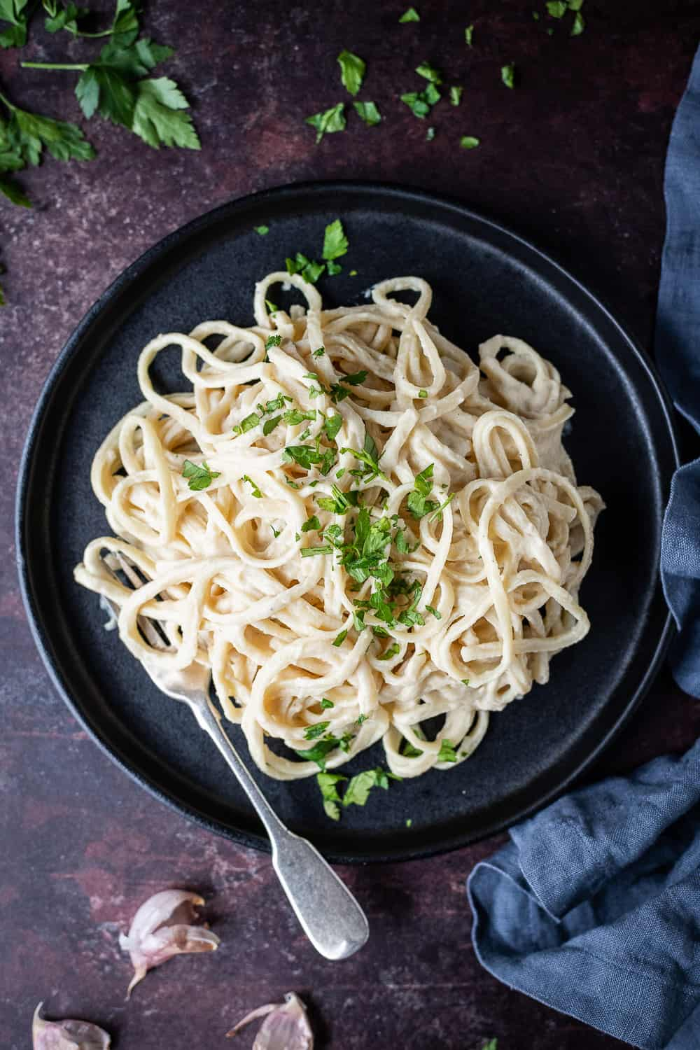Cauliflower alfredo linguine on a black plate with a fork and chopped parsley on a dark brown background.