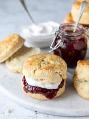 Close up of a vegan scone filled with raspberry jam and cream.