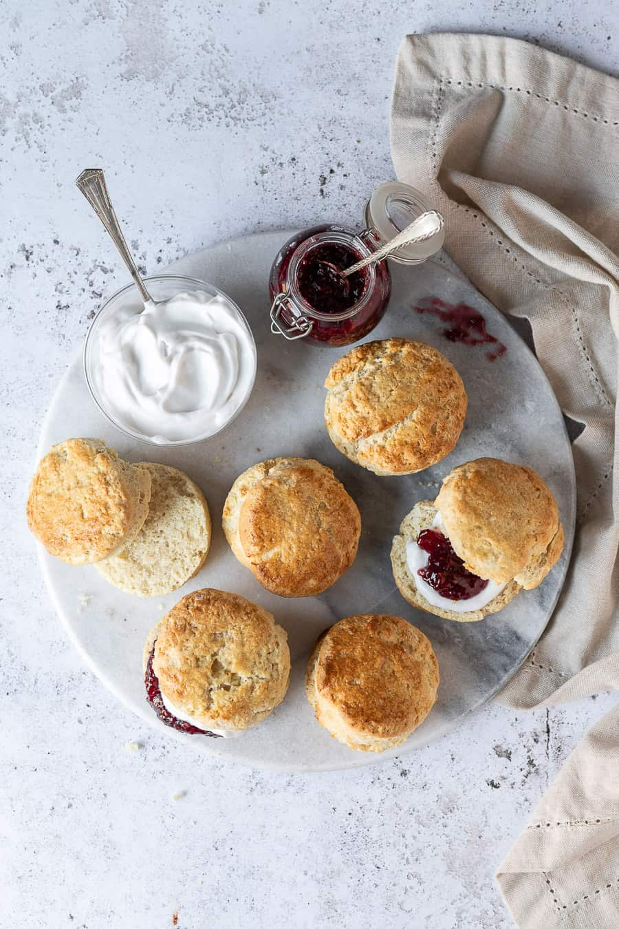 Vegan scones on a marble platter on a white background with a cream cloth, a bowl of cream and a jar of raspberry jam.