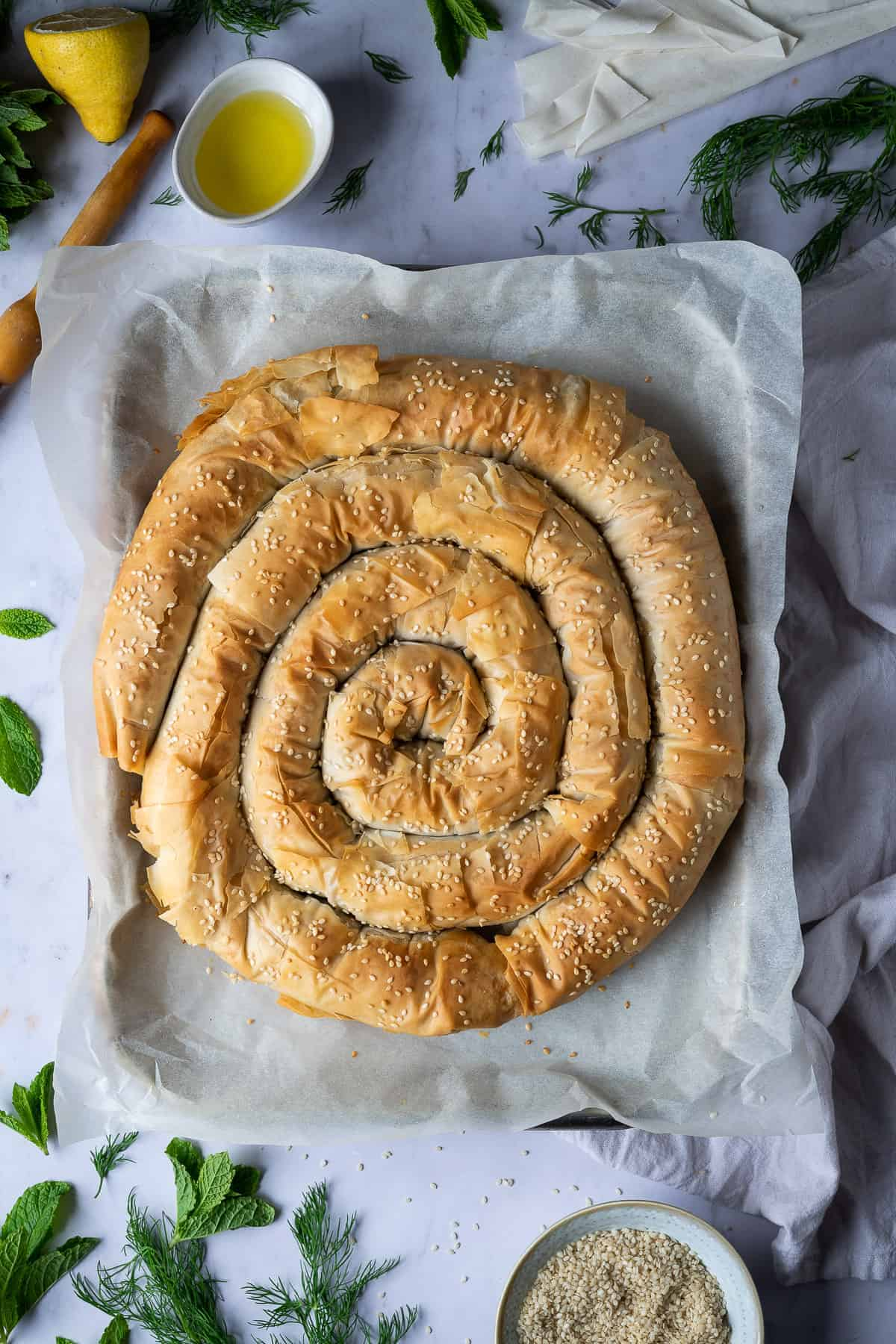vegan spanakopita spiral on a baking sheet on a marble background with fresh herbs.