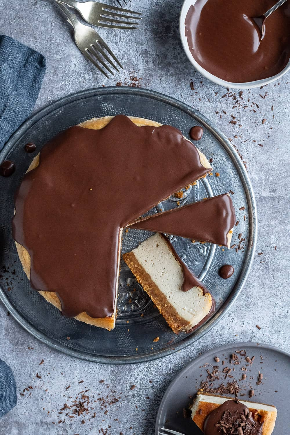 Top down shot of vegan Baileys cheesecake cur into slices on a metal plate with one slice on a grey plate and a bowl of chocolate ganache.