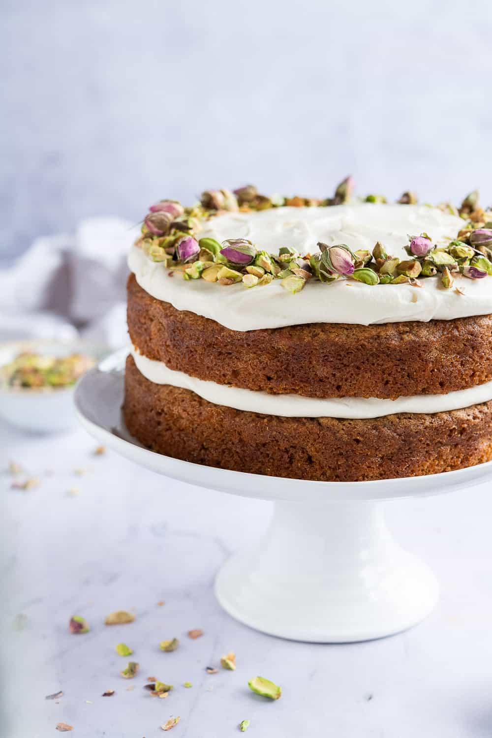 Side shot of vegan carrot layer cake with pistachios and rosebuds on a white cake stand.