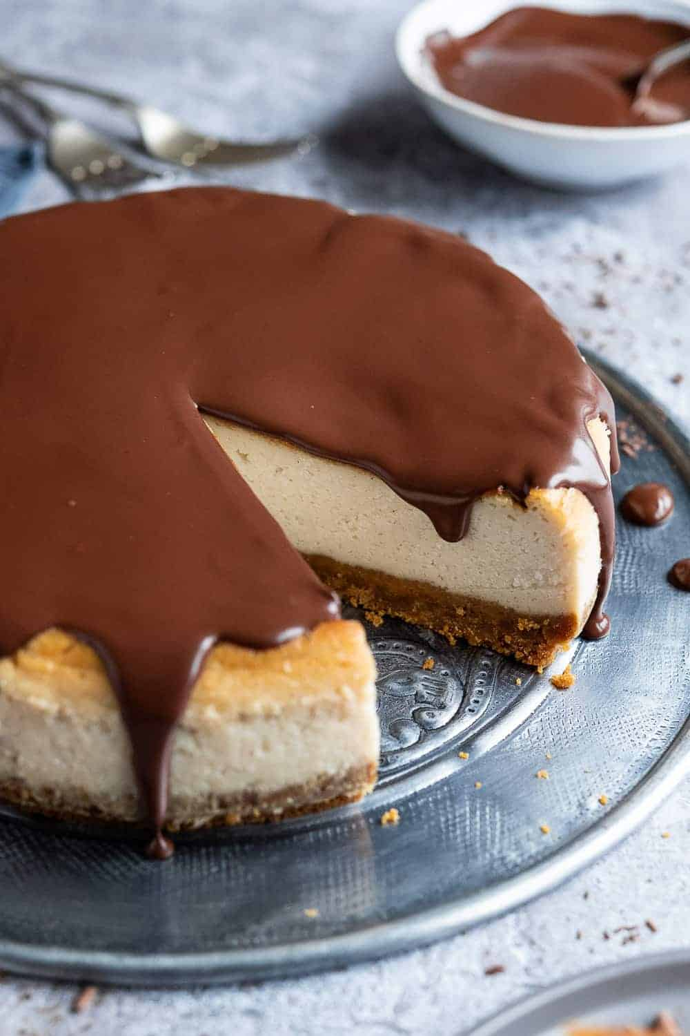 Close up of vegan Baileys cheesecake with Baileys ganache on a metal platter with a slice removed.