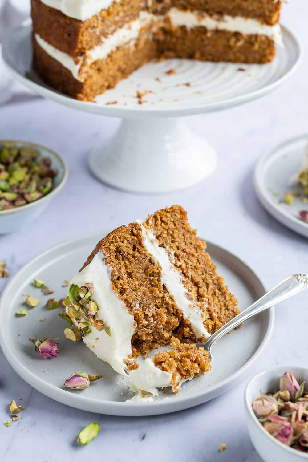 A slice of vegan carrot cake on a grey plate with a fork.