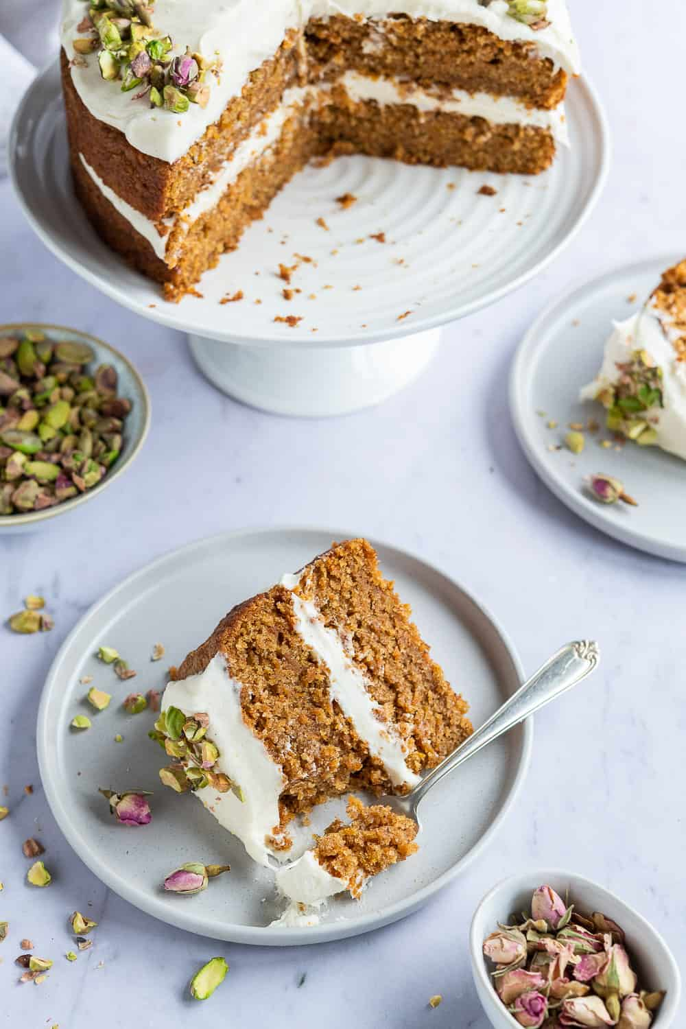 Two slices of vegan carrot cake on grey plates with the rest of the cake on a white cake stand.