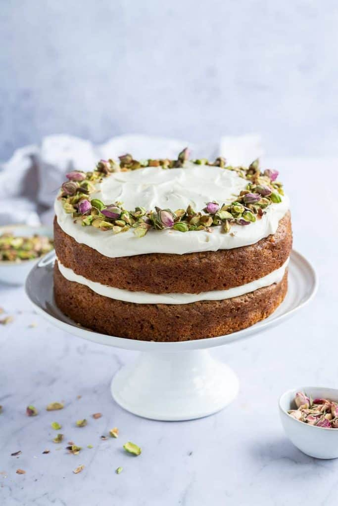Vegan carrot cake with cream cheese frosting, pistachios and rosebuds on a white cake stand on a marble surface.