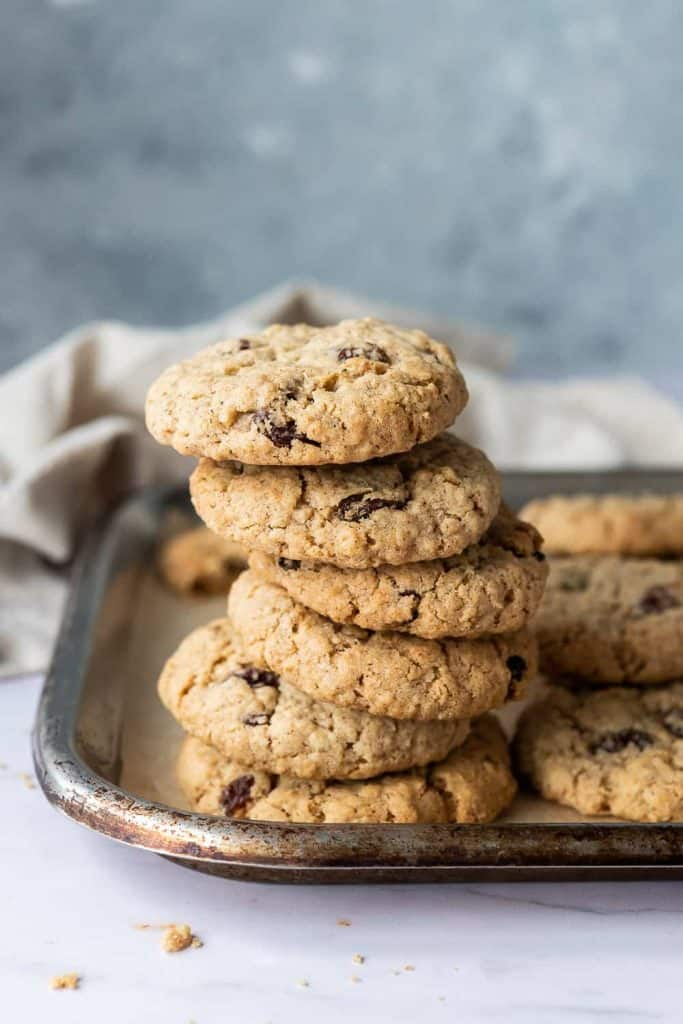 a stack of vegan oatmeal raisin cookies on a metal tray.