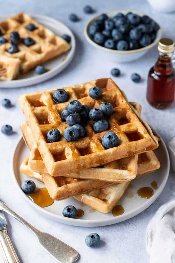 A stack of vegan waffles on a grey plate with blueberries and maple syrup.