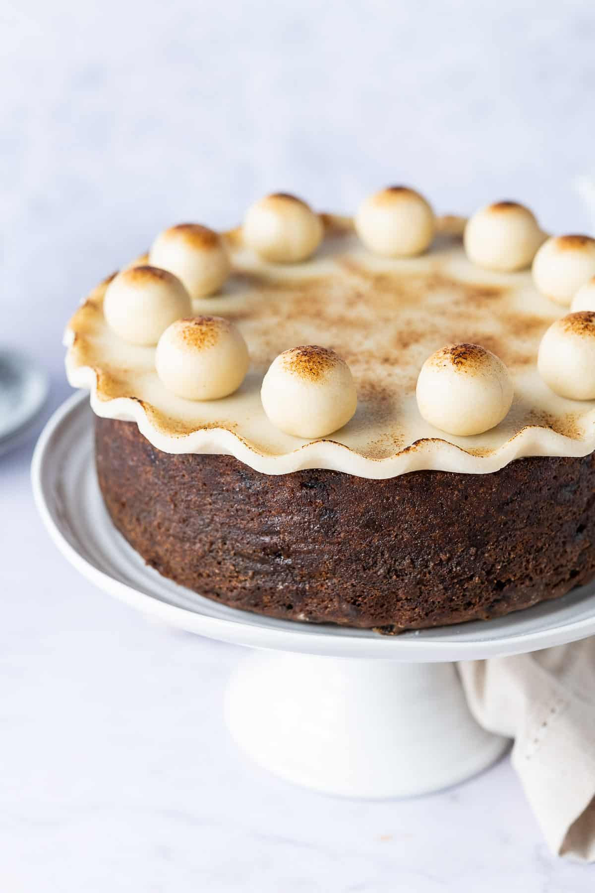 Close up of vegan simnel cake with marzipan decorations on a white cake stand.