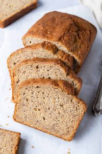 Sliced easy vegan banana bread on a sheet of white baking parchment on a light grey background.