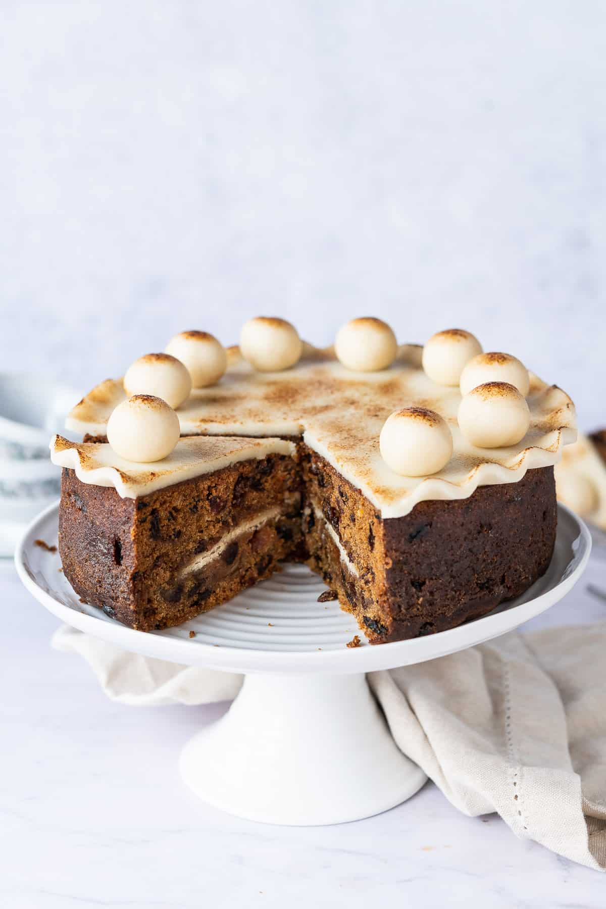 Sliced vegan Simnel cake on a white cake stand on a light grey background