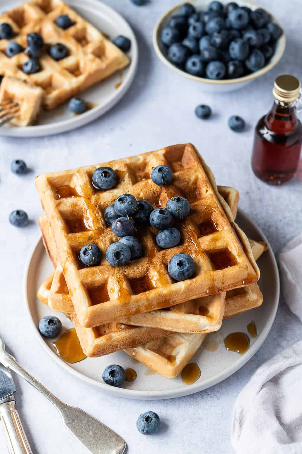 A stack of vegan waffles on a grey plate topped with blueberries and maple syrup