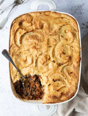 vegan cottage pie in a white dish on a white background with a cream tea towel and forks.