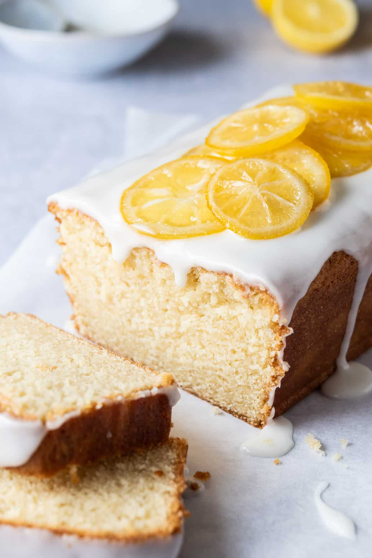 close up of a loaf of vegan lemon pound cake with two slices of cake.